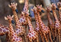 Um girafa de madeira está para fora na multidão de carvings similares Fotografia de Stock Royalty Free