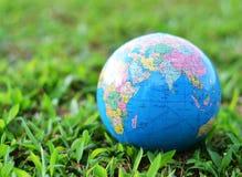 Um globo na grama verde Foto de Stock Royalty Free