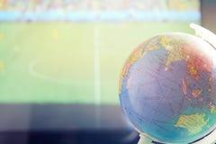 Um globo pequeno com um fundo borrado do campo de futebol imagem de stock