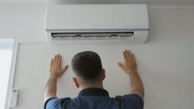 Um gotejamento do homem com suor esfria sob um córrego do ar frio que está ao lado de um condicionador de ar de trabalho video estoque