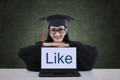Um graduado fêmea que mostra como na tela do portátil fotografia de stock royalty free