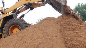 Um grande carregador amarelo derrama para fora uma cubeta da terra, carregador à terra filme