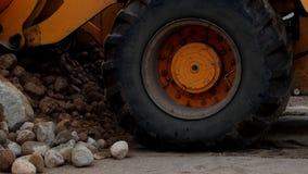 Um grande carregador amarelo recolhe a pedra esmagada em uma cubeta, em um close-up, em umas pedras e em um trator vídeos de arquivo