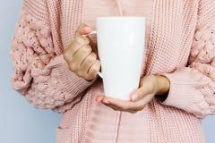 Um grande copo branco para o café ou o chá nas mãos de uma jovem mulher vestida em um casaco de lã feito malha da cor do pêssego fotografia de stock royalty free