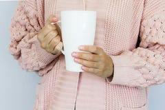 Um grande copo branco para o caf? ou o ch? nas m?os de uma jovem mulher vestida em um casaco de l? feito malha da cor do p?ssego foto de stock royalty free