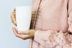 Um grande copo branco para o caf? ou o ch? nas m?os de uma jovem mulher vestida em um casaco de l? feito malha da cor do p?ssego imagens de stock royalty free