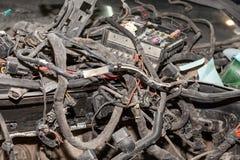 Um grande emaranhado de embaraça fios coloridos da fiação do carro encontra-se na cabine do carro desmontado com conectores e tom fotos de stock