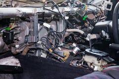 Um grande emaranhado de embaraça fios coloridos da fiação do carro encontra-se na cabine do carro desmontado com conectores e tom foto de stock royalty free