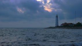 Um grande farol branco no litoral brilha a luz amarela filme