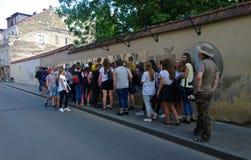 Um grande grupo de turista-estudantes ao lado da constituição famosa do Uzupis Fotos de Stock