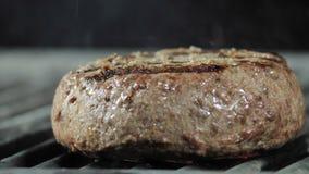 Um grande hamburguer suculento do hamburguer ? close-up grelhado, com os tenazes de brasa do ferro para girar o rissol para o out video estoque