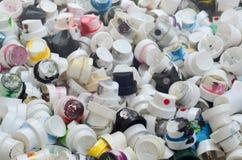 Um grande número tampões das latas da pintura do aerossol para grafittis Manchado com os bocais coloridos da pintura encontre-se  Fotografia de Stock Royalty Free