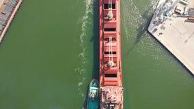 Um grande portador de maioria entra no porto da carga com rebocadores Metragem aérea 4k filme