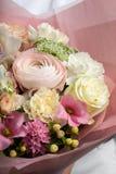Um grande ramalhete de espalhamento bonito das flores nas mãos de uma menina, o trabalho de um florista fotos de stock royalty free