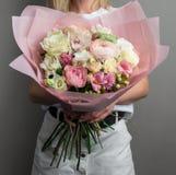 Um grande ramalhete de espalhamento bonito das flores nas mãos de uma menina, o trabalho de um florista fotografia de stock