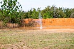 Um grande respingo da água em uma poça da argila vermelha imagens de stock