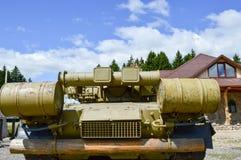 Um grande tanque de guerra militar verde do metal do ferro com um canhão é montado estacionou ao lado da casa da casa de campo co imagem de stock