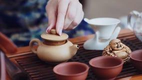 Um grupo bonito para a cerimônia de chá está em uma tabela de madeira pequena Na chaleira derrame a água a ferver vídeos de arquivo
