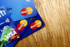 Um grupo cartões de crédito de MasterCard e de visto espalhou em uma tabela de madeira Foto de Stock