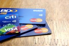 Um grupo cartões de crédito de MasterCard e de visto espalhou em uma tabela de madeira Fotografia de Stock Royalty Free