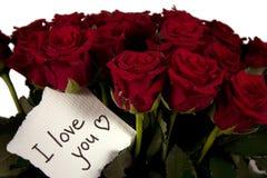 Um grupo das rosas no vaso de vidro com cartão do amor Foto de Stock Royalty Free