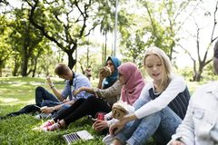 Um grupo de adolescentes diversos toma parte num piquenique no parque imagens de stock