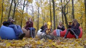 Um grupo de amigos descansa em sopros perto de um fogo e bebe da garrafa térmica filme