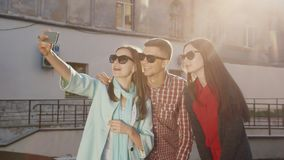 Um grupo de amigos faz o selfie, eles faz uma cara engraçada Os raios vermelhos do sol em um fundo de uma construção velha video estoque