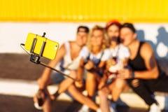 Um grupo de amigos faz um selfie que senta-se no pavimento, empresa dos jovens que tomam imagens com uma vara do selfie, cheerf fotografia de stock
