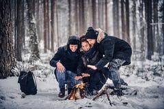 Um grupo de amigos felizes encenou um acampamento no meio de uma floresta nevado foto de stock royalty free