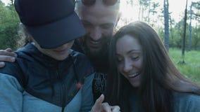 Um grupo de amigos felizes está vendo fotos no smartphone Povos bonitos que riem na natureza em fazer do parque vídeos de arquivo