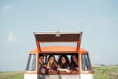 Um grupo de amigos novos em um roadtrip através do campo, olhando fora da janela imagem de stock