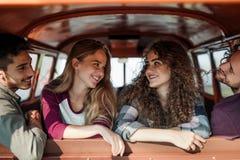 Um grupo de amigos novos em um roadtrip através do campo, sentando-se em um carro imagens de stock royalty free