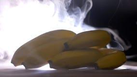Um grupo de bananas suculentas e maduras no fundo do fumo e do frescor, evaporação, close-up, movimento lento video estoque