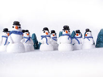 Um grupo de bonecos de neve na neve Imagens de Stock Royalty Free
