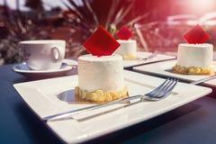 Um grupo de brownies com chocolate vermelho nas placas brancas e em uma xícara de café em uma tabela em um café da rua Por do sol Foto de Stock Royalty Free