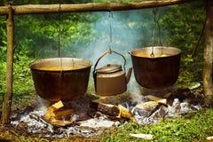Um grupo de caldeirões e a chaleira são pendurados em cima do fogo Foto de Stock Royalty Free