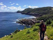 Um grupo de caminhantes explora as costas ásperas de Terra Nova fora de St John imagem de stock