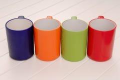 Um grupo de canecas, variedade de copos coloridos, vermelho, verde, azul, ou Foto de Stock