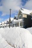 Um grupo de casas após uma tempestade da neve com um cargo da lâmpada na parte dianteira Fotografia de Stock