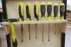 Um grupo de chaves de fenda que penduram na oficina imagens de stock