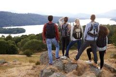 Um grupo de cinco amigos adultos novos da raça misturada admira a vista após a chegada na cimeira após uma caminhada da montanha, fotografia de stock royalty free