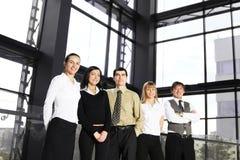 Um grupo de cinco businesspersons novos em um escritório Fotografia de Stock Royalty Free