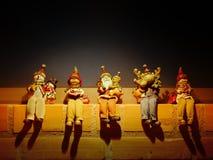 Um grupo de cinco figuras da decoração do Natal assentadas em uma parede de tijolo com fundo escuro fotografia de stock