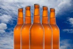 Um grupo de cinco garrafas de cerveja em uma formação de diamante no backg do céu Foto de Stock