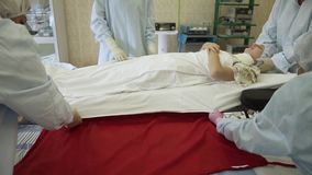 Um grupo de cirurgiões desloca o paciente após a cirurgia a uma cama para o transporte filme