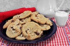 Um grupo de cookies da noz dos pedaços de chocolate em uma placa com um vidro Fotos de Stock
