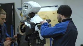 Um grupo de coordenadores cria um robô ou um androide moderno Artigos quebrados da verificação e do reparo Fabrique e fabrique de filme