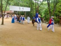 Um grupo de coreanos tradicionalmente vestidos anda através da vila para a mostra do turista imagens de stock