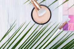 Um grupo de cosméticos decorativos para a composição do dia encontra-se no fundo de um galho verde de uma planta em uma tabela br imagens de stock
